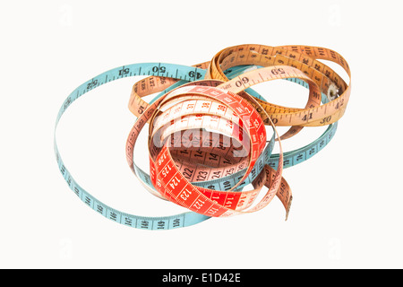 three coiled tape measures in blue red and yellow - Stock Photo