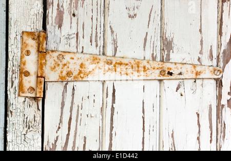 large rusted metal hinge on peeling wooden door - Stock Photo