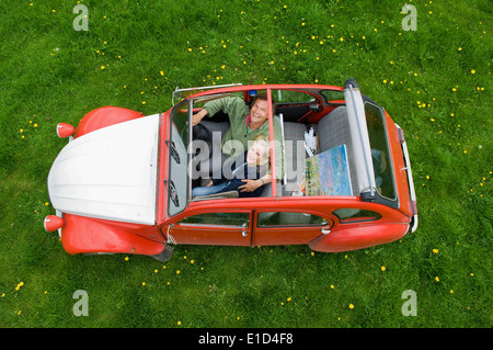 View from above of two people, a couple in a car with the roof open. - Stock Photo