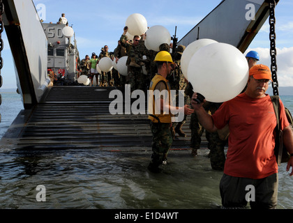 U.S. Navy Seabees, Marines and civilians from nongovernmental organizations carry water jugs off a landing craft - Stock Photo
