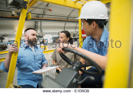 Workers meeting at forklift in manufacturing plant - Stock Photo