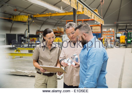 Workers examining metal parts in manufacturing plant - Stock Photo