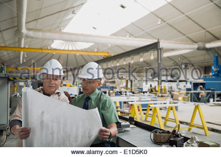 Workers reviewing blueprints in manufacturing plant - Stock Photo