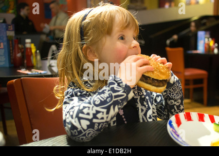 Four 4 year old girl in restaurant eating cheese burger - Stock Photo