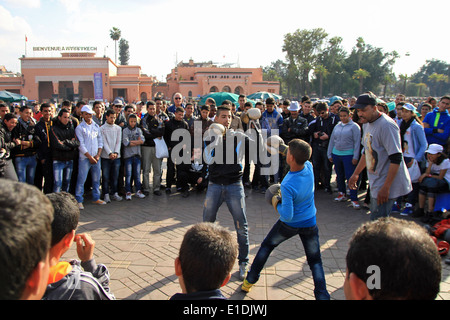 Two boys box in the Djemaa el Fna square, Marrakech, Morocco - Stock Photo