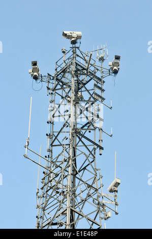 Communications tower cell tower with mobile phone antennae and CCTV cameras - Stock Photo