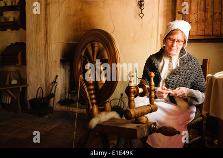 A woman dressed in 19th Century clothes spins wool using a traditional spinning wheel  in the Ulster American Folk - Stock Photo