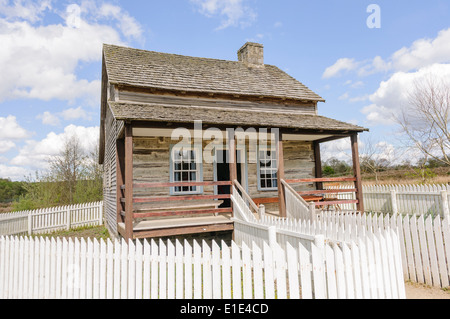 Old fashioned wooden American farm house with a white picket fence in the Ulster American Folk Park, Northern Ireland - Stock Photo