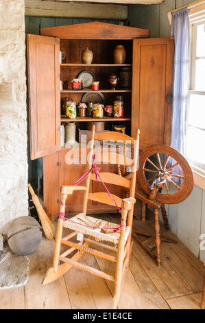 Rocking chair and spinning wheel inside an old fashioned house - Stock Photo