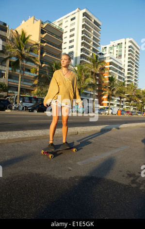 RIO DE JANEIRO, BRAZIL - FEBRUARY 08, 2014: Young Brazilian woman on skateboard passes in front of Ipanema beachfront - Stock Photo