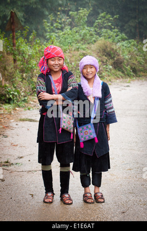 A couple of Black Hmong girls in traditional clothing, just outside of Sapa, Lao Cai Province, Vietnam. - Stock Photo