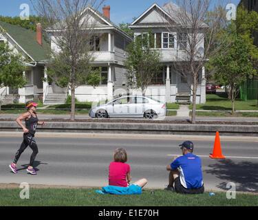 Calgary, Alberta, Canada. 01st June, 2014. Spectators watch ultramarathon runner racing along Memorial Drive in - Stock Photo