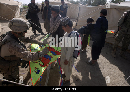 U.S. Marine Corps 1st Sgt. Jonathan Wyble assists an Afghan child with his kite on kite day in Marjah, Afghanistan, - Stock Photo