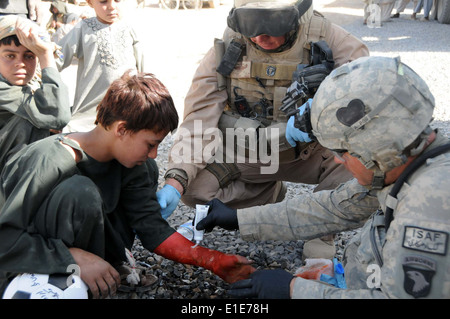 U.S. Navy Hospital Corpsman 2nd Class Chris Lutton, right, assigned to Naval Mobile Construction Battalion 18, and - Stock Photo