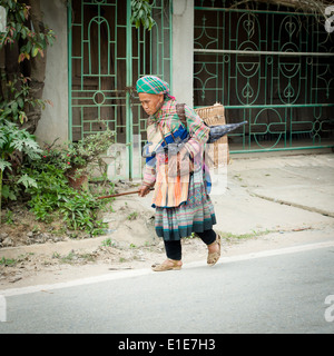 An old Flower Hmong woman walks home from the Bac Ha Sunday Market in Bac Ha, Lao Cai Province, Vietnam. - Stock Photo
