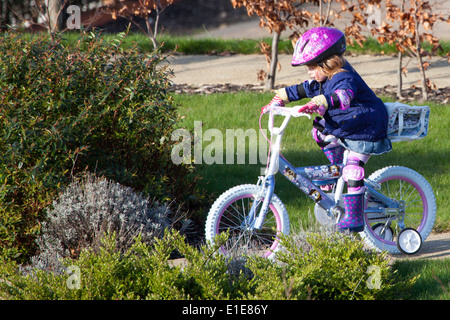 Four 4 year old girl riding her bike - Stock Photo