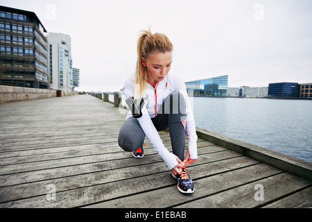 Young woman tying her shoelaces before a run along waterfront. Female runner preparing foe sprint. Fit female athlete - Stock Photo