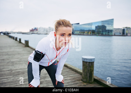 Young female runner stopping for a rest while out on a run along river. Fitness woman taking a break from training - Stock Photo