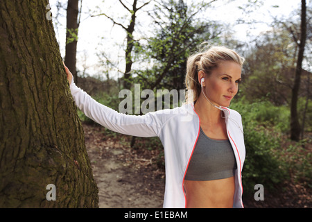 Fit female taking a break after running on forest trail. Pretty young woman wearing headphones listing to music - Stock Photo
