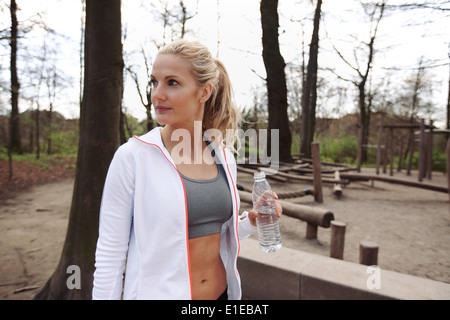 Young woman in park with water bottle looking away. Fitness woman relaxing after training session in nature. - Stock Photo