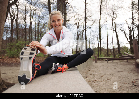 Happy and fit woman stretching her legs before training session in nature. Beautiful caucasian athlete exercising - Stock Photo
