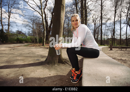 Female runner taking a break from running in forest. Beautiful young female athlete sitting with a water bottle. - Stock Photo