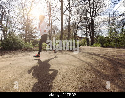 Healthy young woman jogging in park. Fitness female model running in forest. Caucasian fitness model exercising - Stock Photo