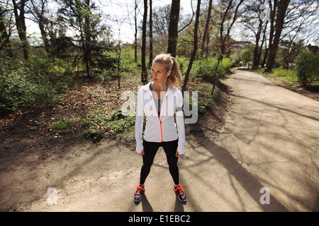 Young woman in exercise clothing standing on a forest trail looking away. Fitness female on outdoors training sessions. - Stock Photo
