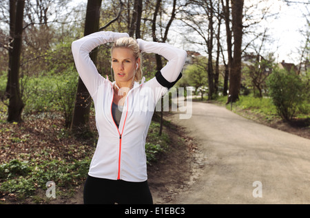 Young fitness woman tying hair before her run. Fit young female athlete focusing on her run in forest. - Stock Photo