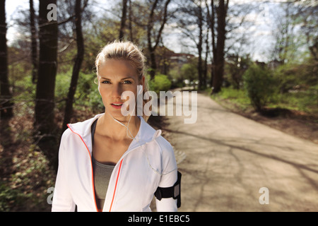 Portrait of pretty young woman in sports clothing wearing earphones while on fitness routine in forest. Young female - Stock Photo