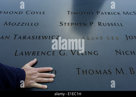 Detail of visitor's hand and names of victims at the 9/11 Memorial in New York, killed at the locations of terrorist - Stock Photo