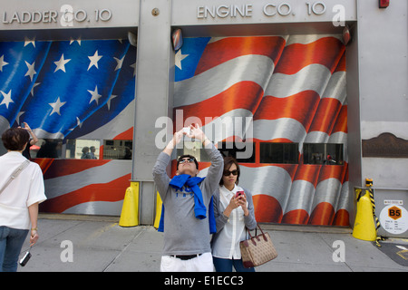 In front of a fire station, visitors use smartphones to record the new One World Trade Center opposite the 9/11 - Stock Photo