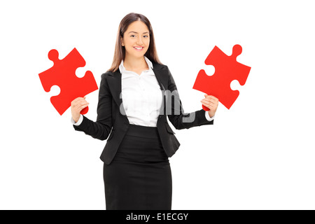 Young businesswoman holding two pieces of puzzle - Stock Photo