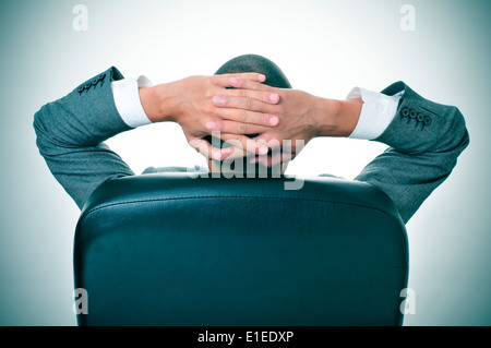 a businessman relaxing in the chair of his office with his hands behind his head - Stock Photo