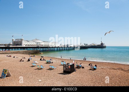 People relaxing at the beach next to the Pier of Brighton, East Sussex, UK - Stock Photo