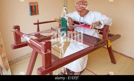 An Omani weaver, wearing a traditional muzzar (headcloth), at work in Muscat, in the Sultanate of Oman. - Stock Photo