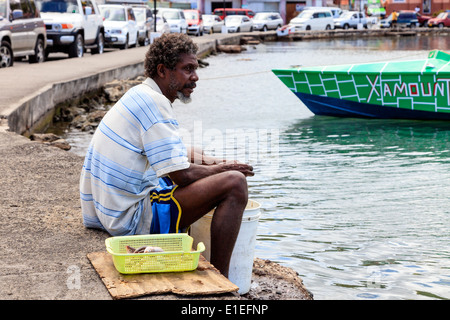 Local fisherman sitting on the promenade and gutting fish at Carenage bay, St George, Grenada, West Indies - Stock Photo