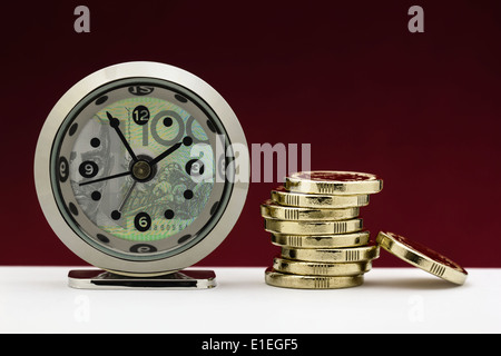 Clock and currency note with stack of gold coins illustrating the concepts of time is money or financial deadline/pressure. - Stock Photo