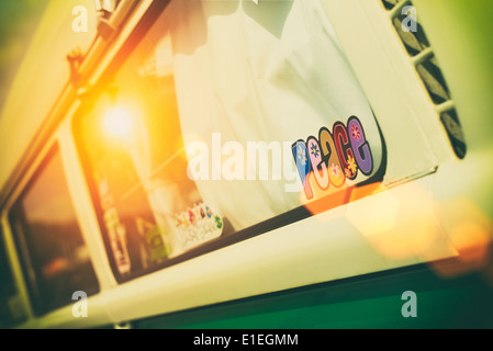 Peace sticker in the window of a VW Campervan with added nostalgic filter and dusky sun flare. - Stock Photo