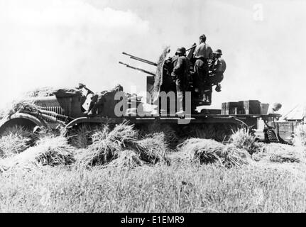 The picture from Nazi news reporting shows German soldiers crewing an anti-aircraft gun for the defence against - Stock Photo
