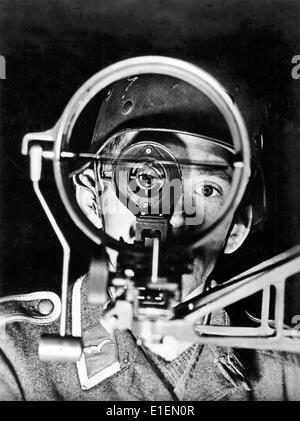 The picture from the Nazi news reports shows a German gunman at a flak gun looking through the scope to aim the - Stock Photo