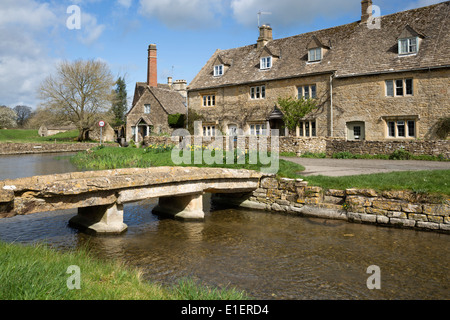 Stone bridge and cotswold cottages by the River Eye - Stock Photo