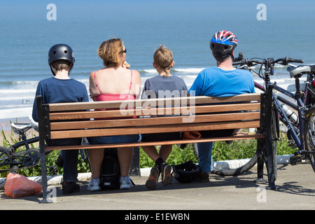 Family with bikes having picnic on bench overlooking Saltburn beach. Saltburn by the Sea, North Yorkshire, England, - Stock Photo