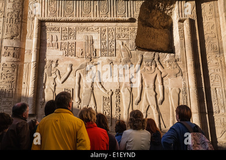 Tourist group observed ancient relief at Temple of Kom Ombo, Egypt - Stock Photo