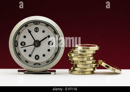 Clock with a stack of gold coins illustrating the concepts of time is money or financial deadline/pressure. - Stock Photo