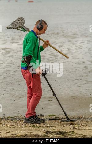 Man using metal detector on beach, Poole Harbour, UK - Stock Photo