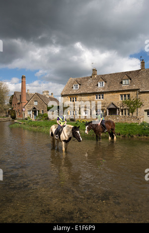 Horses in the River Eye with the Old Mill Museum - Stock Photo