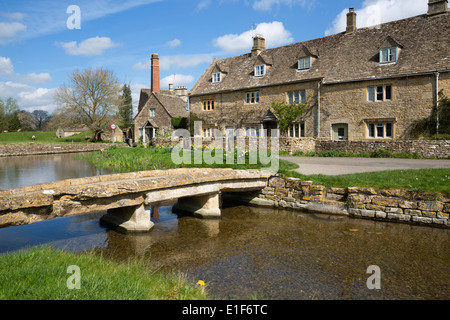 Stone bridge and cotswold cottages on the River Eye - Stock Photo