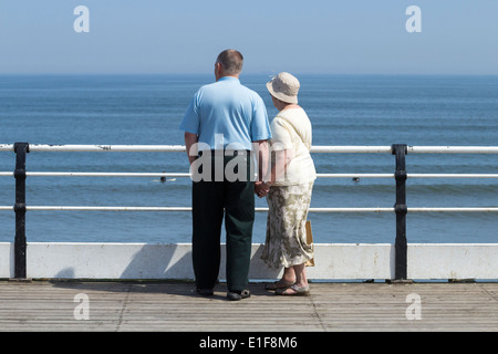 Elderly couple holding hands watching surfers from Saltburn`s Victorian pier - Stock Photo