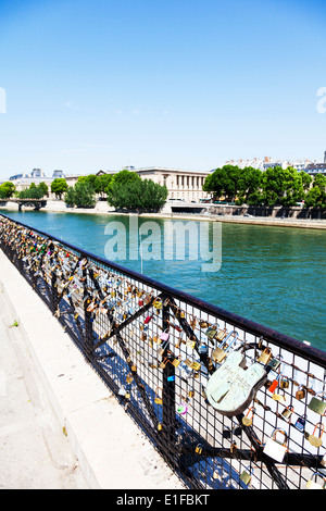 Love locks padlocks on fence overlooking the river Seine Paris France - Stock Photo